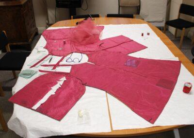 The bright raspberry pink silk taffeta lining of the tabard.